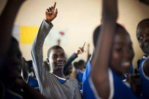 A boy raising his hand in class